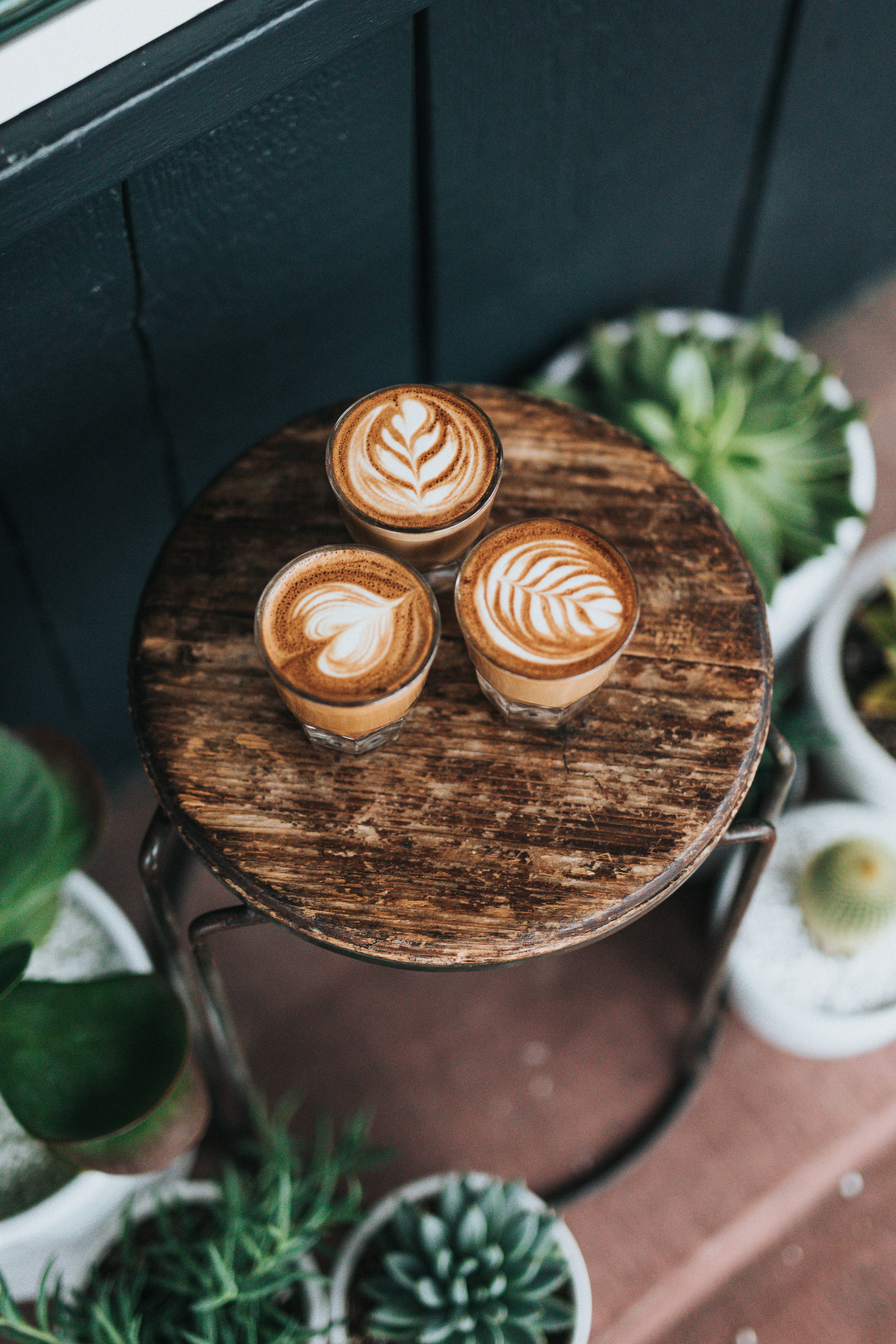 three cups of coffees on round brown wooden stools