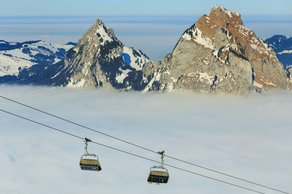 two gray cable cars near rock mountains during daytime