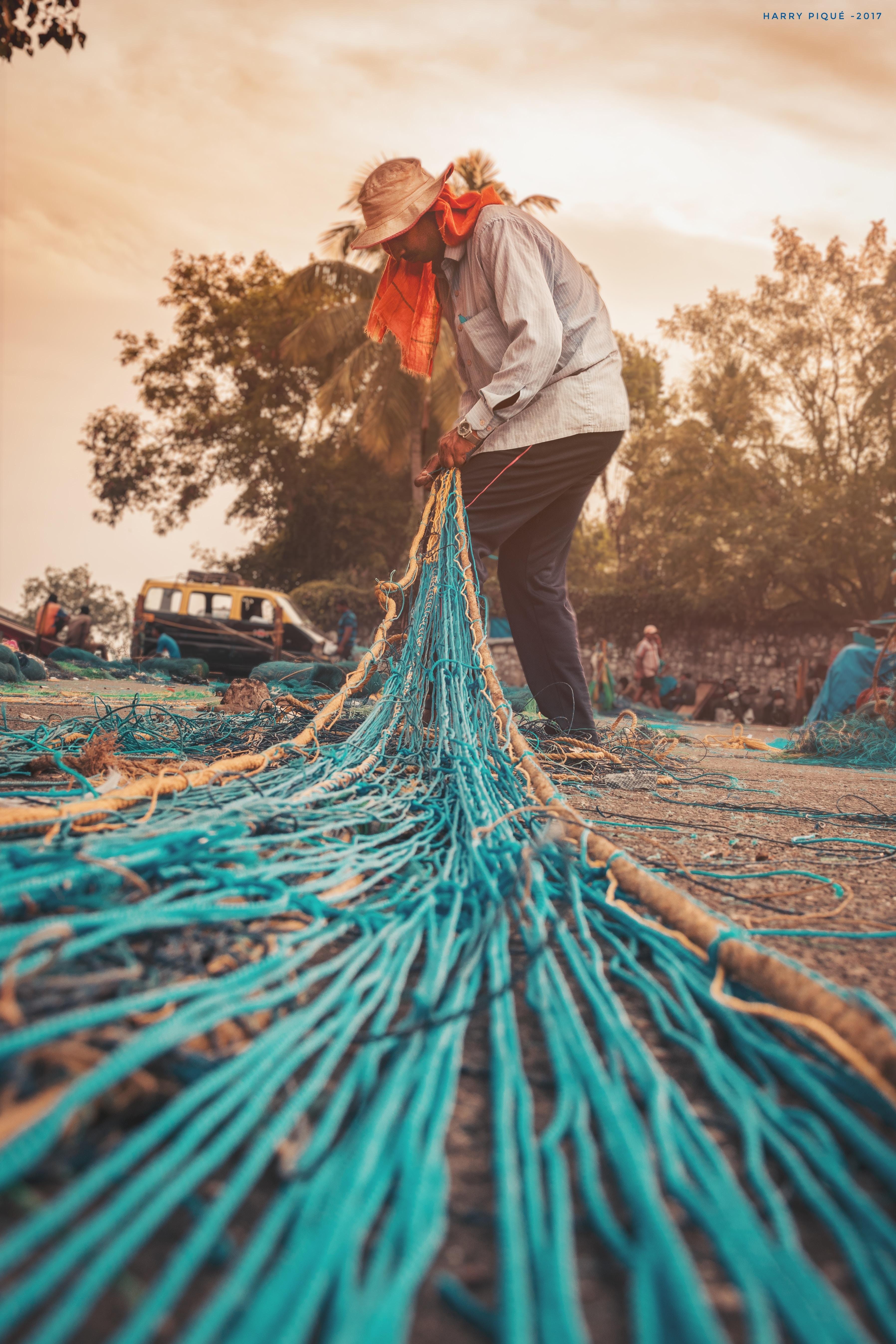 man knitting blue fishing net