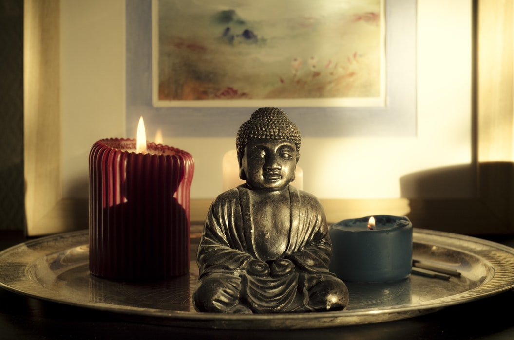 image of candle and small Buddha statue
