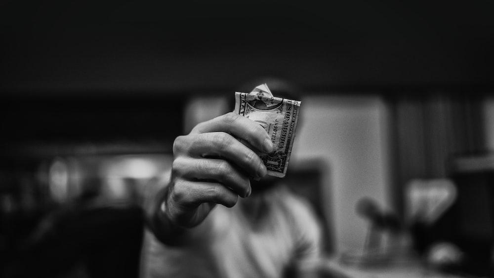 man holding 1 US dollar banknote
