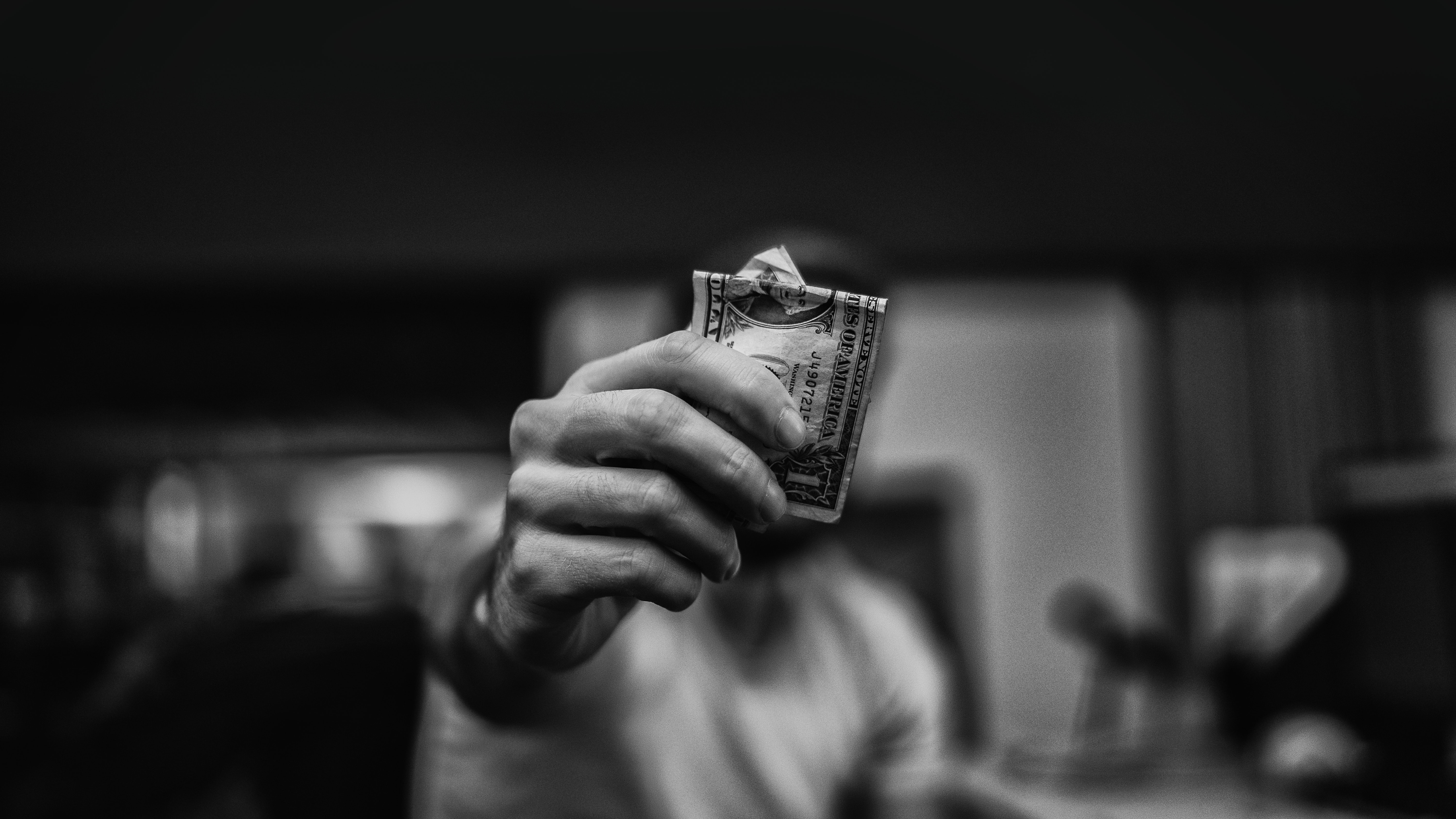 Black and white photograph of a man holding a dollar bill near the camera lens.