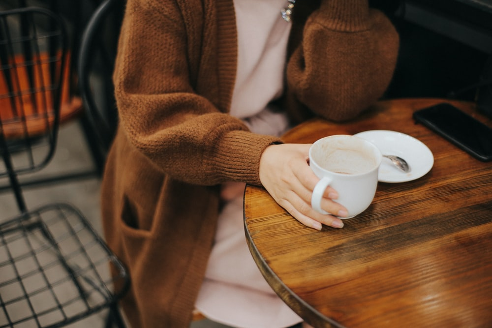 woman sitting on chair while holding white mug
