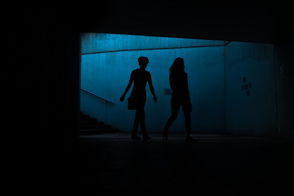 silhouette of two persons underpass