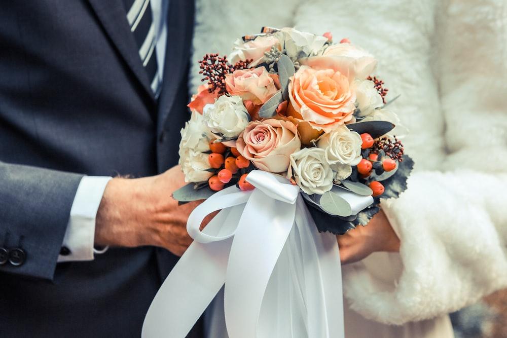 person holding orange and white flower arrangement