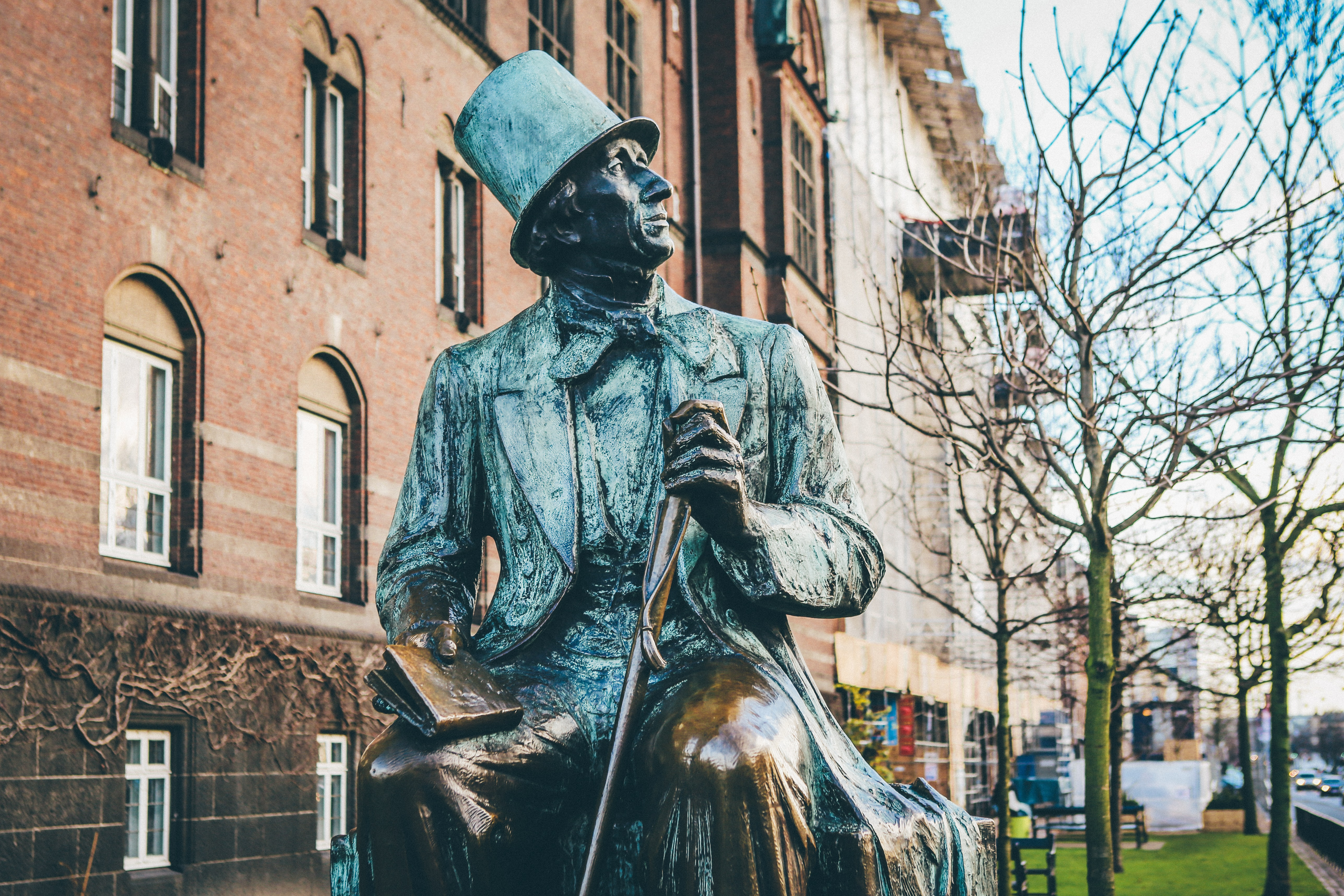 man in top hat and coat holding book and cane sitting statue