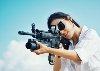 woman sniping at rifle scope