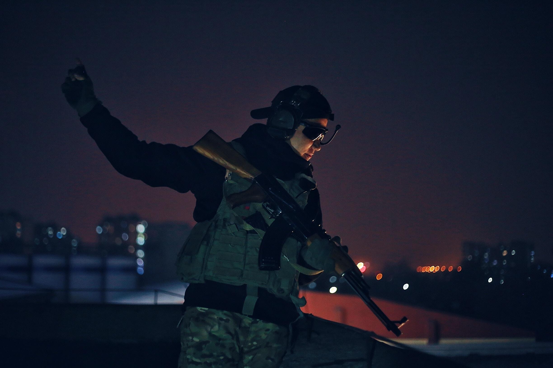 man holding rifle at nighttime