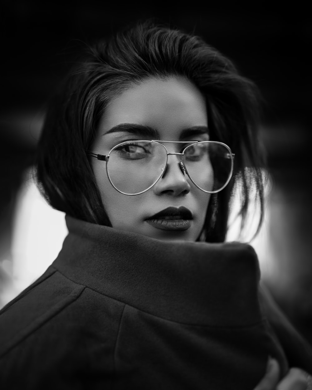 grayscale photo of woman wearing coat and eyeglasses