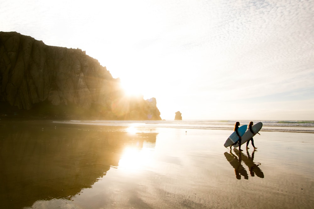 two people carrying surfboards while walking on seashore