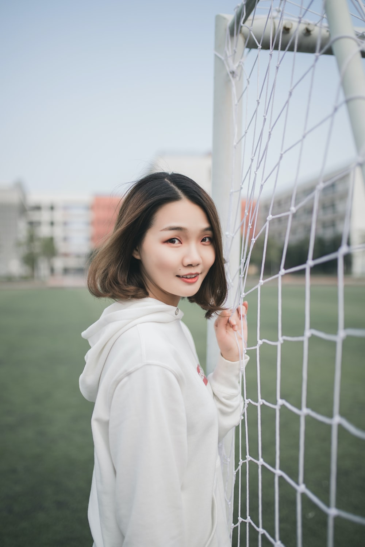 man in white pullover hoodie standing beside white goal net