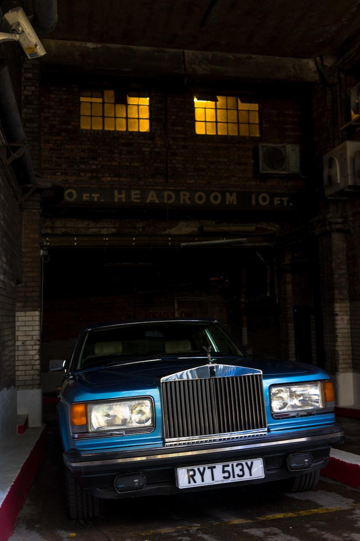 classic blue car parked near Headroom building