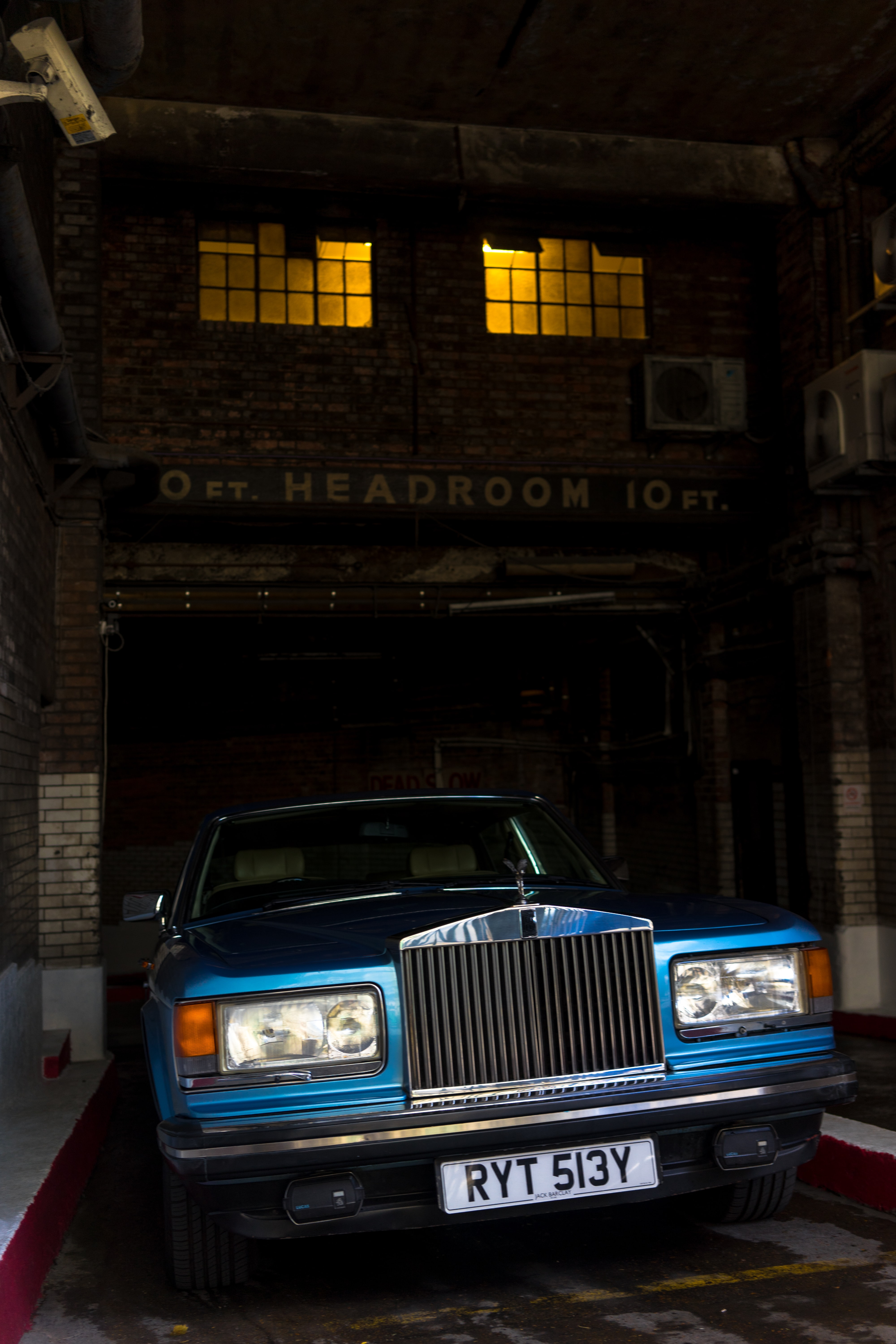 classic blue car parked near Headroom building