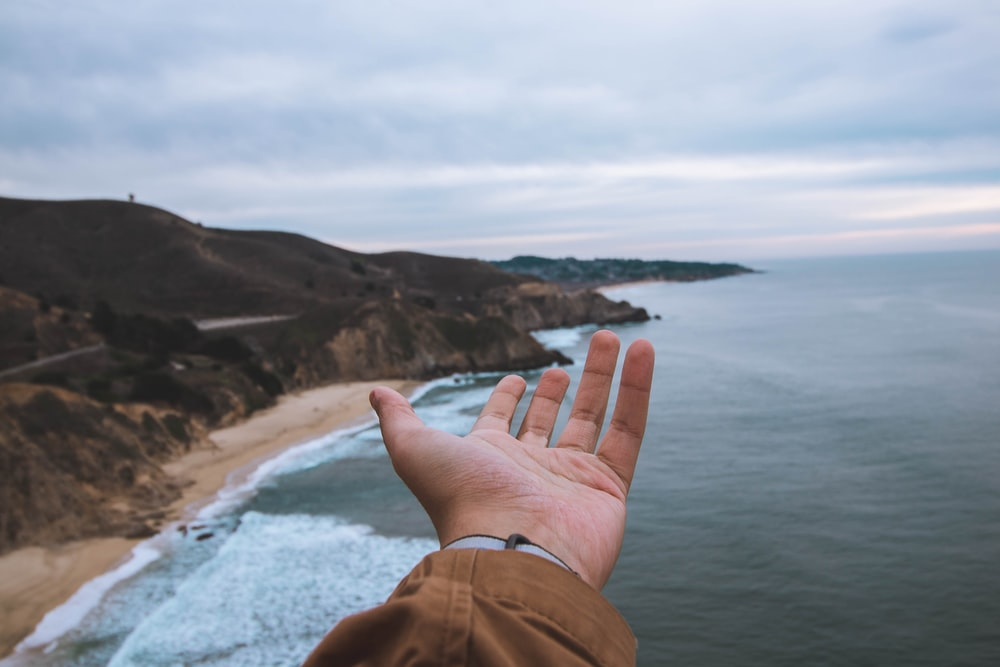 person hand front of sea and cliff