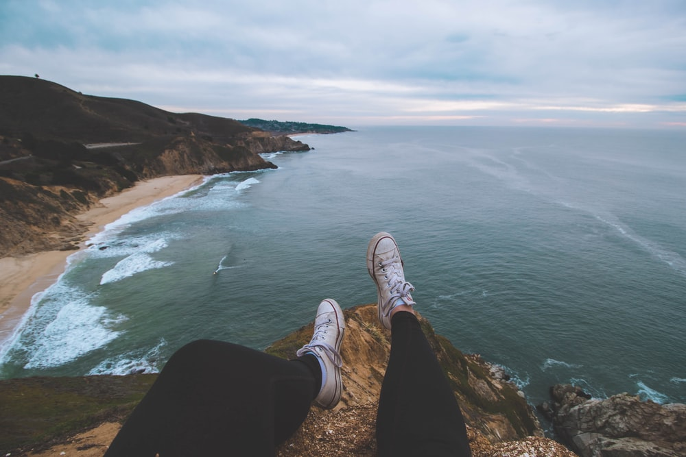 person sitting on cliff rock