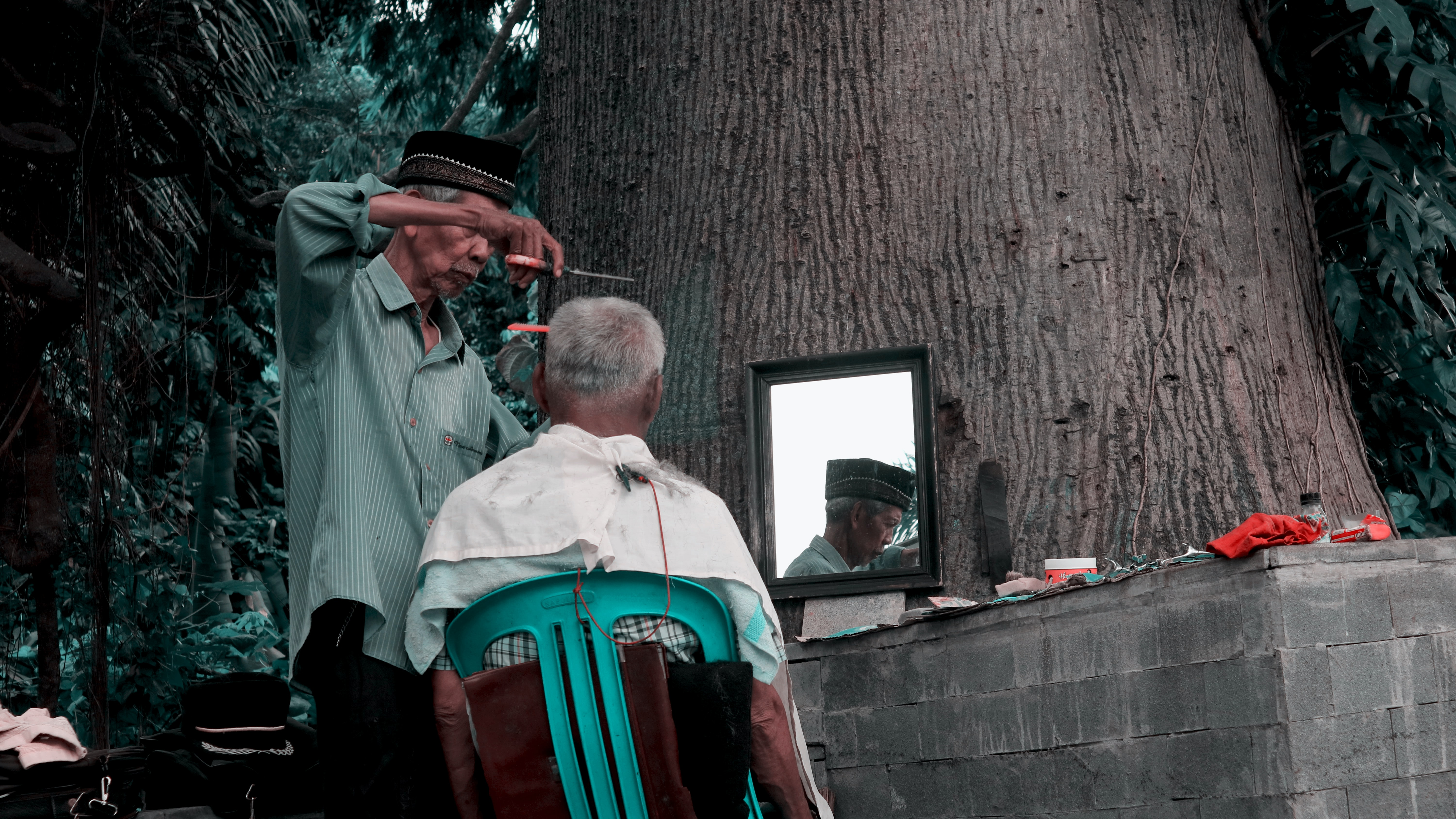 man sitting on green chair facing mirror while the other man standing cutting's man hair at daytime