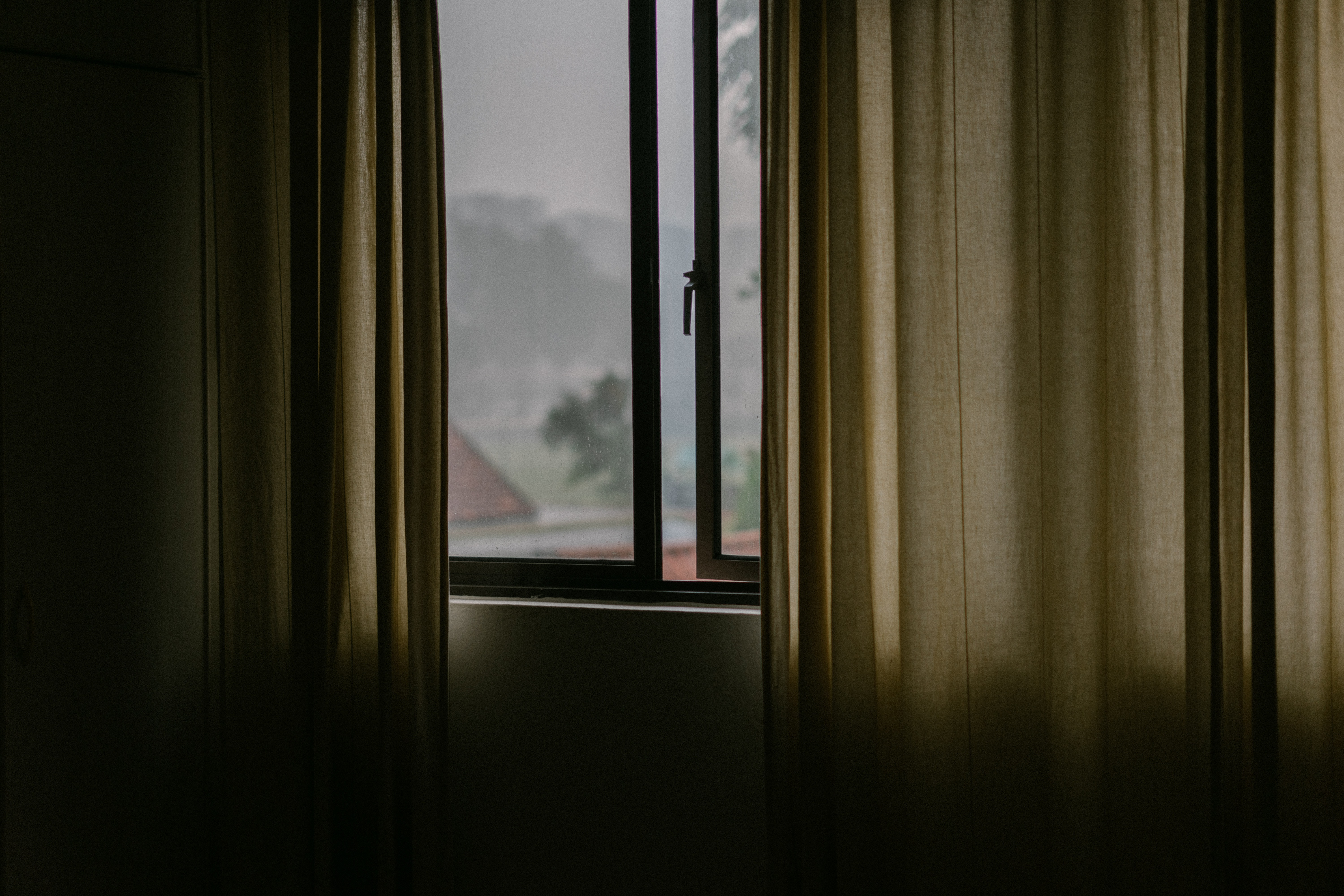 black metal framed glass window open with brown curtain