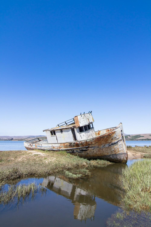 abandoned boat beside green grass field
