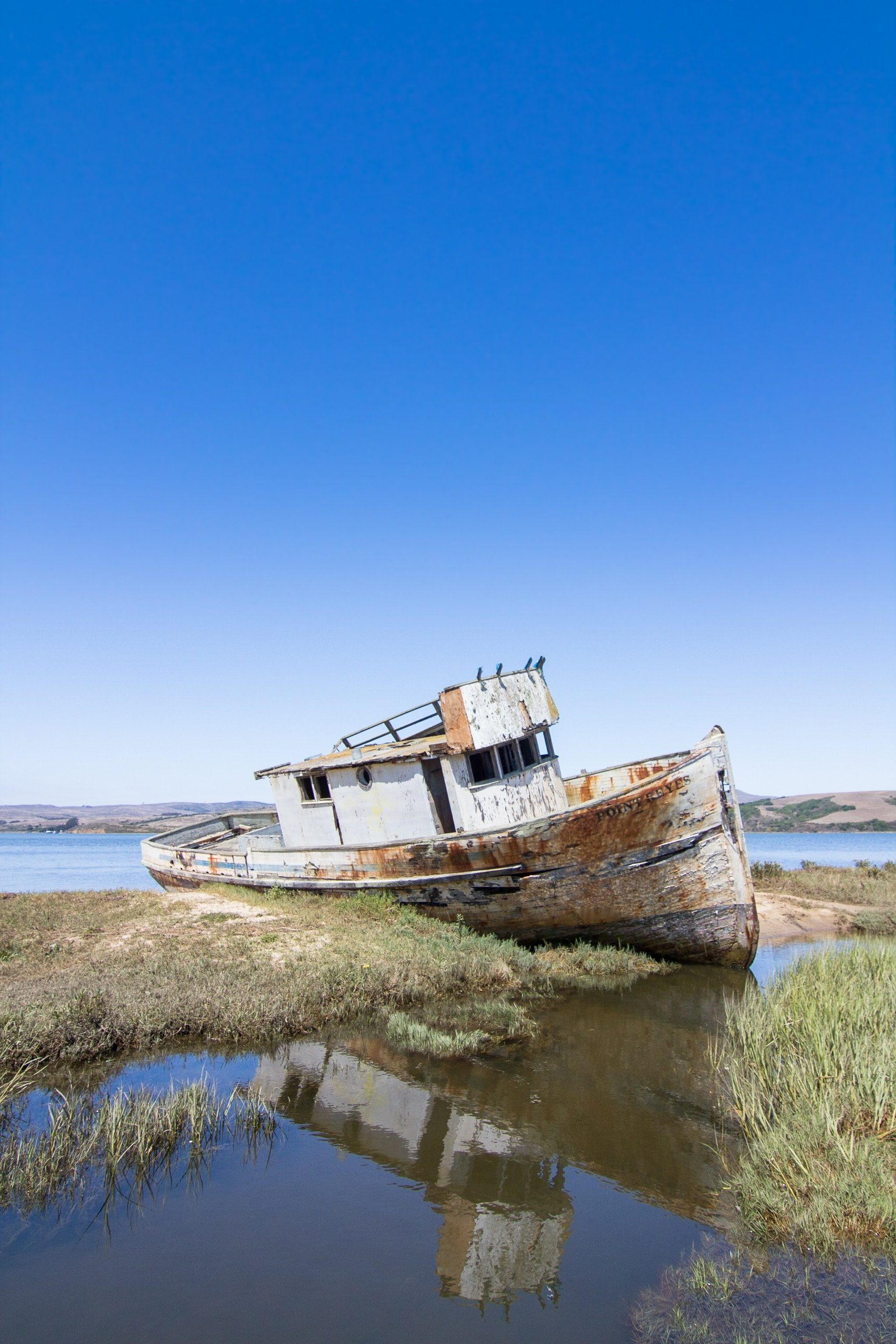 abandoned boat beside green grass field