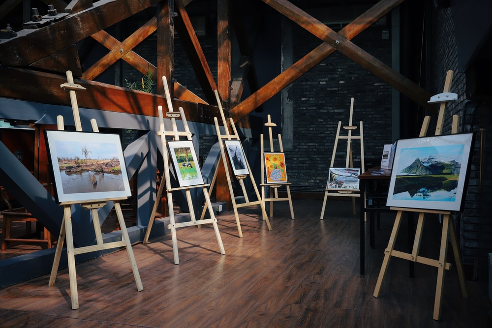 five assorted paintings on easels