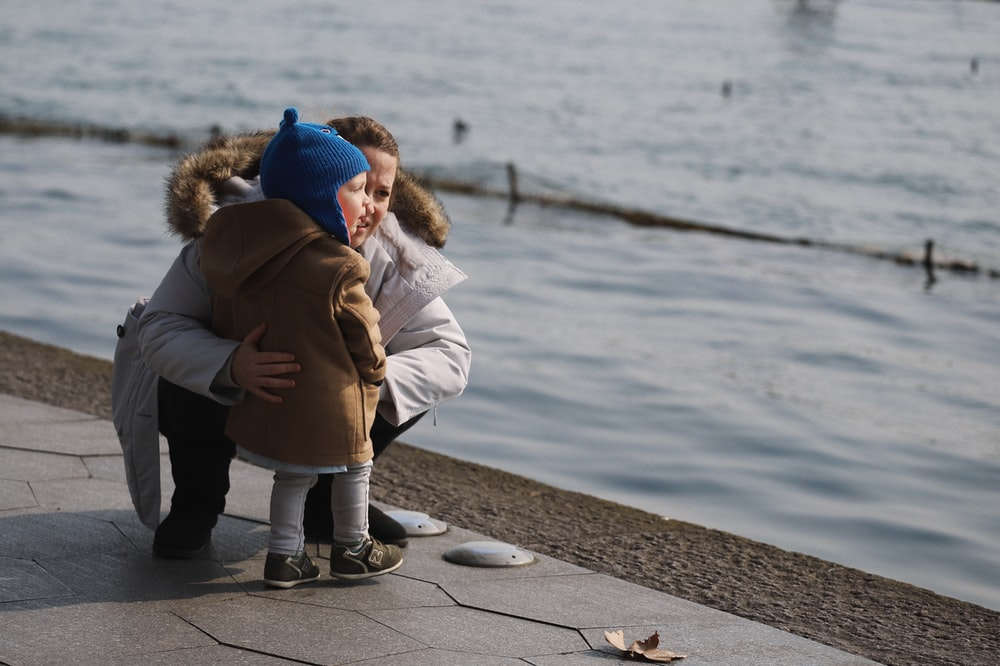 child standing on concrete bay together with sitting woman