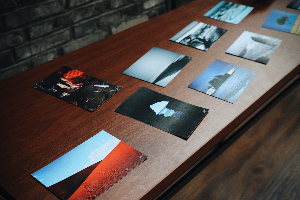 assorted posters on brown wooden table