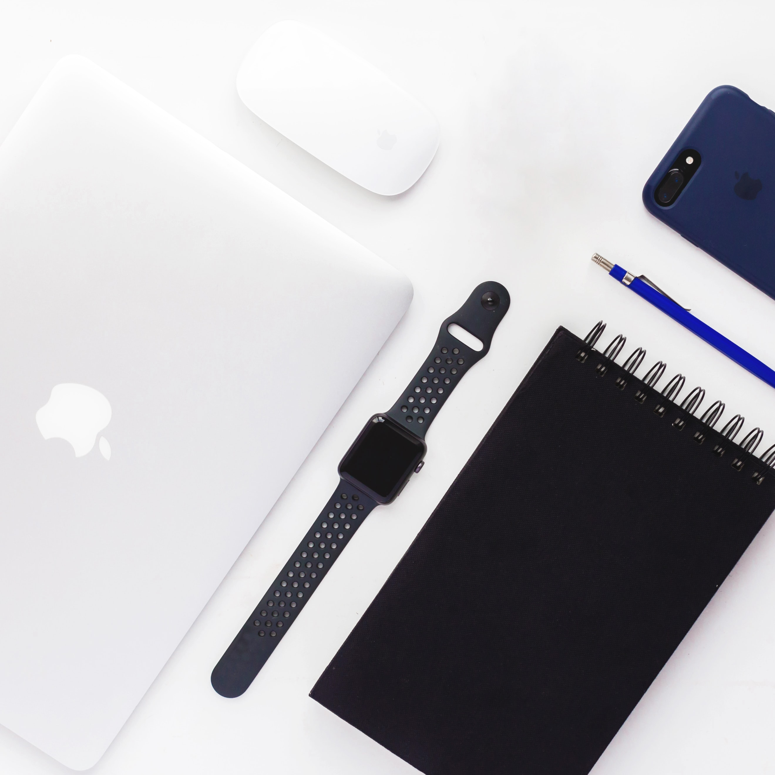 flat lay photography of space gray aluminum case Apple Watch with Nike Sport Band, spiral book, MacBook White, Apple Magic Mouse, and black iPhone 7 Plus with blue case
