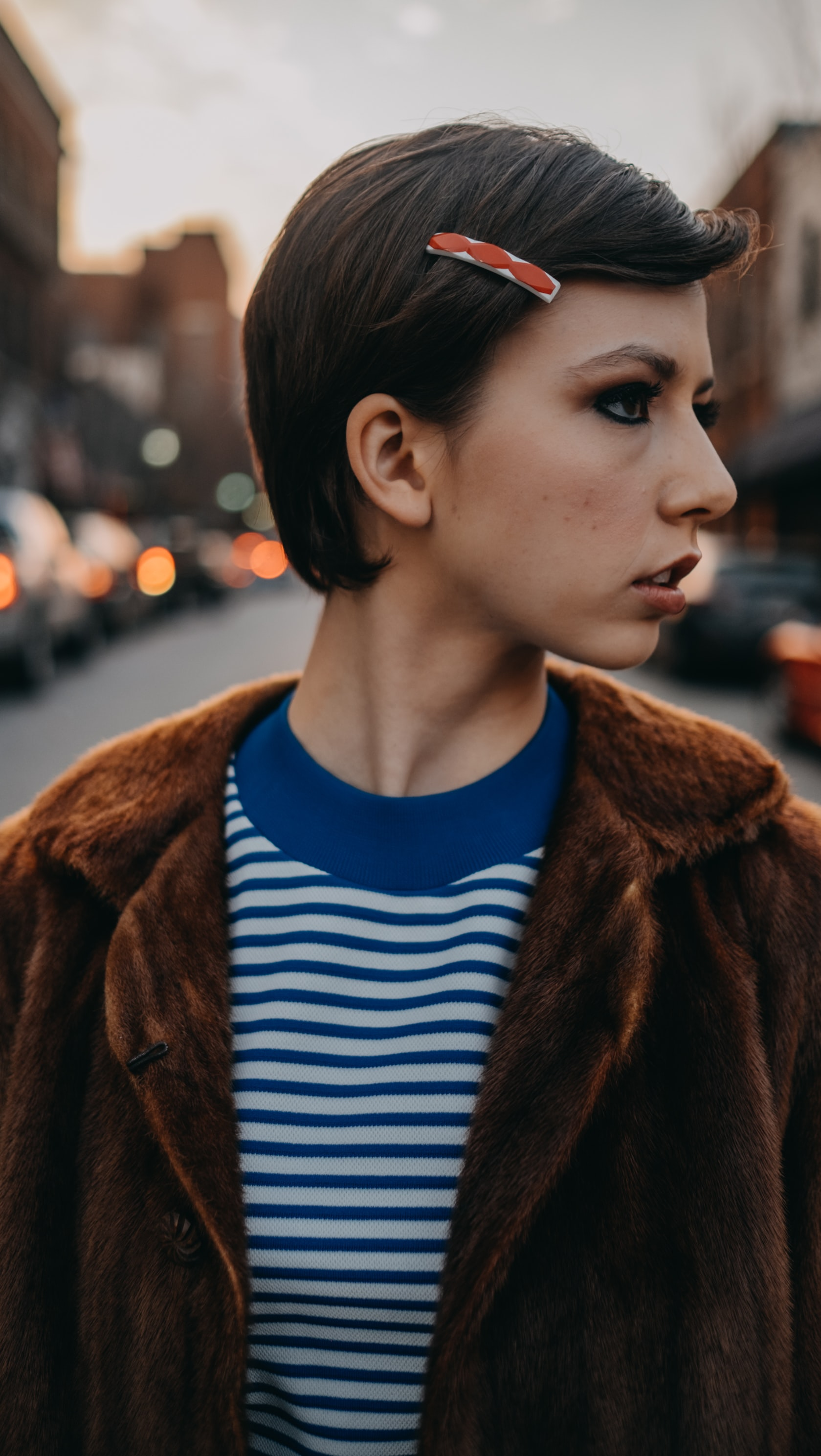 selective focus of woman wearing blue and white stripe top and brown coat