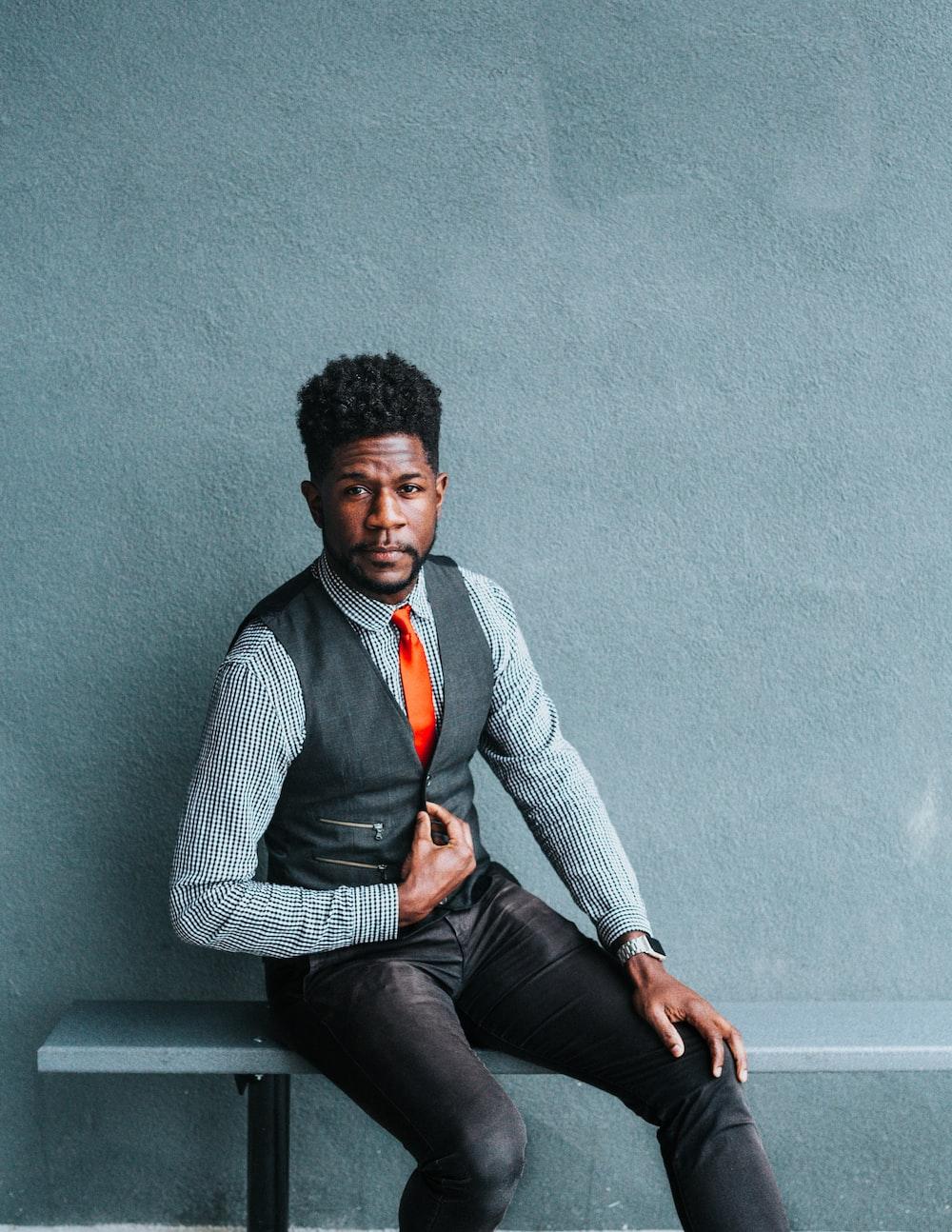 man wearing vest sitting on bench