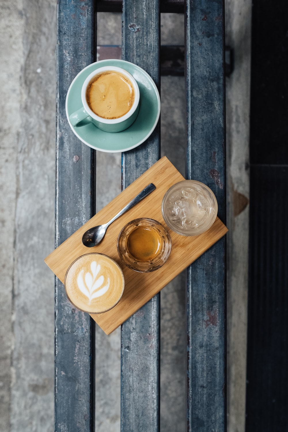 three clear drinking glasses on brown wooden plate beside mug