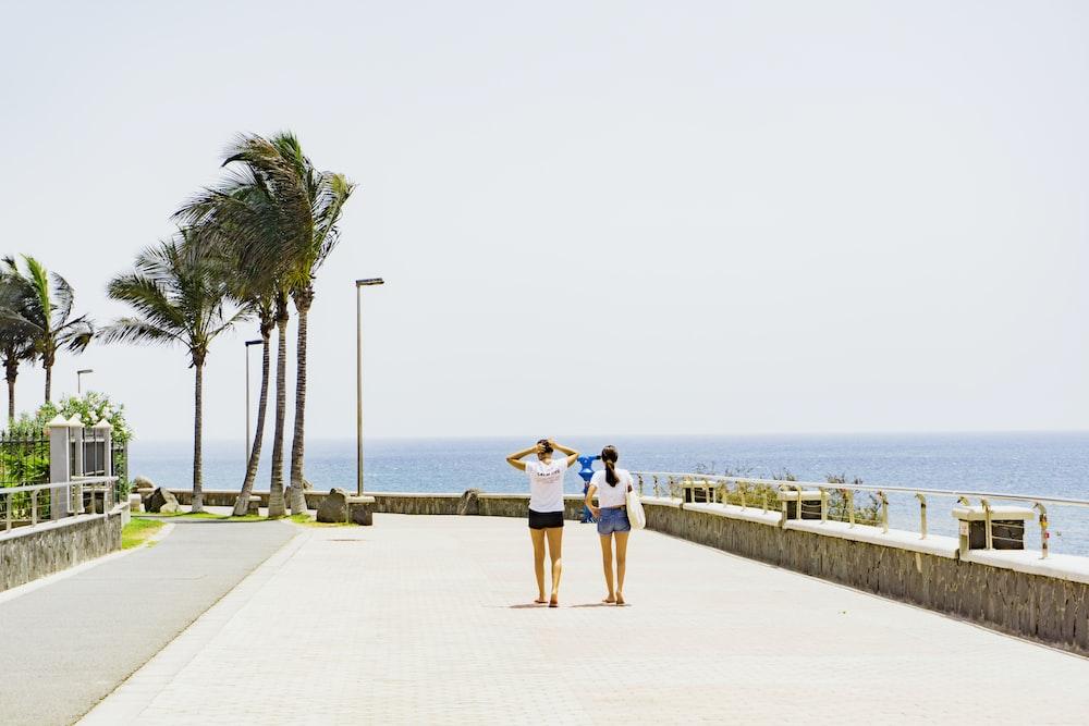 two women walking beside body of water