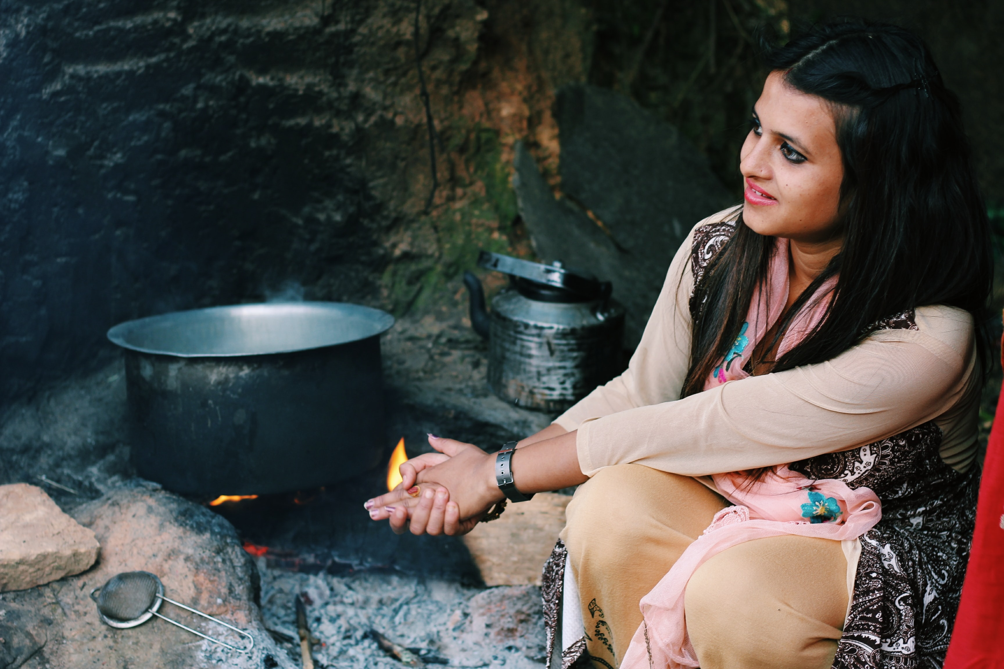 woman sitting near cook pot