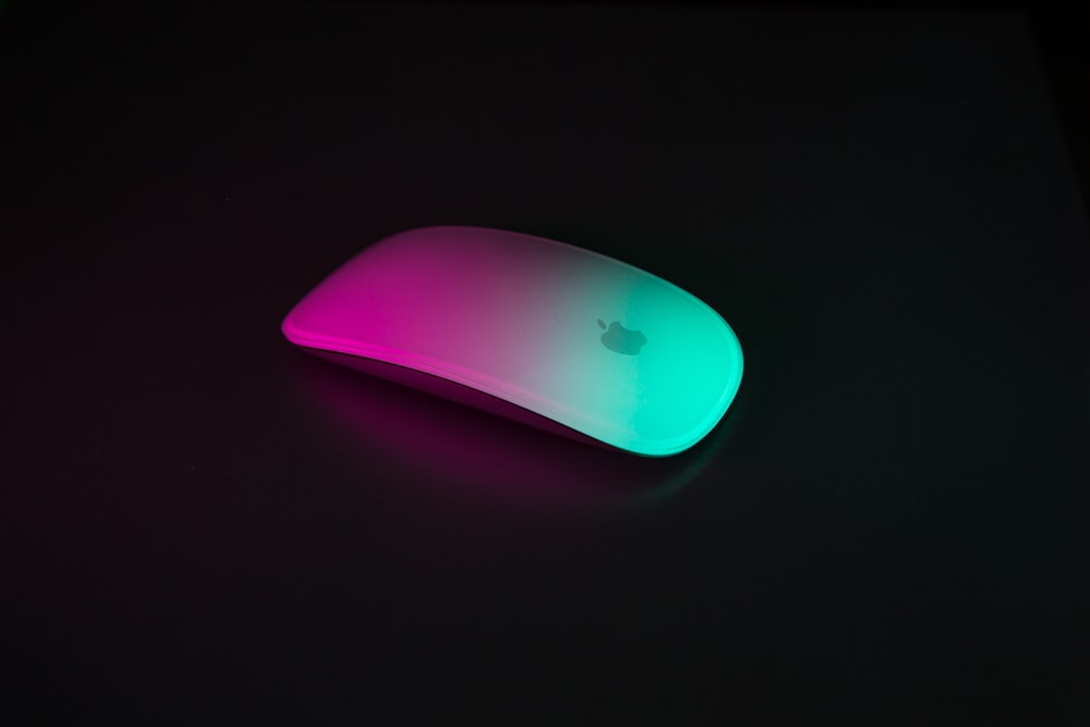 pink and green light reflected on Apple Magic Mouse