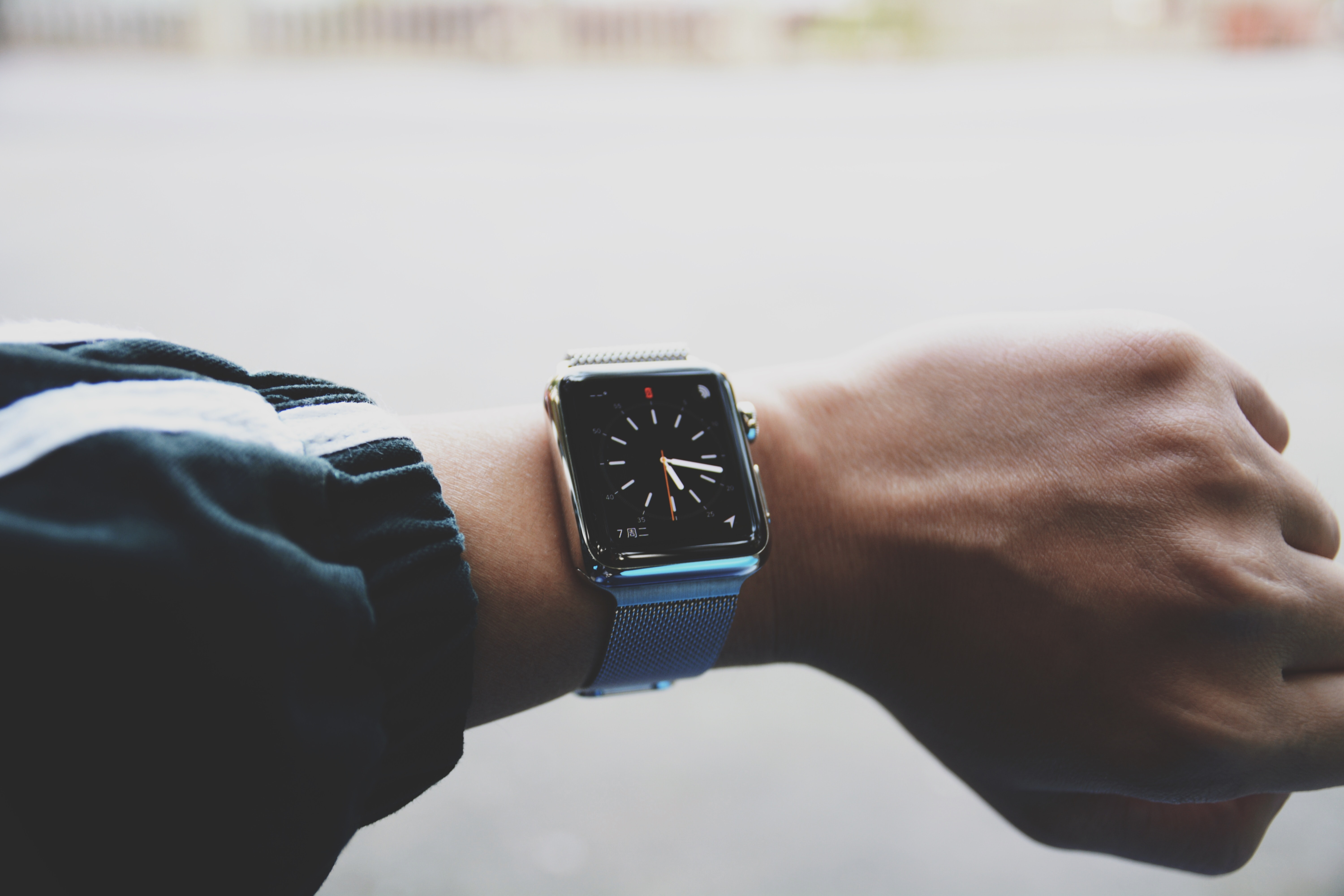 shallow focus photo of person wearing smartwatch watch