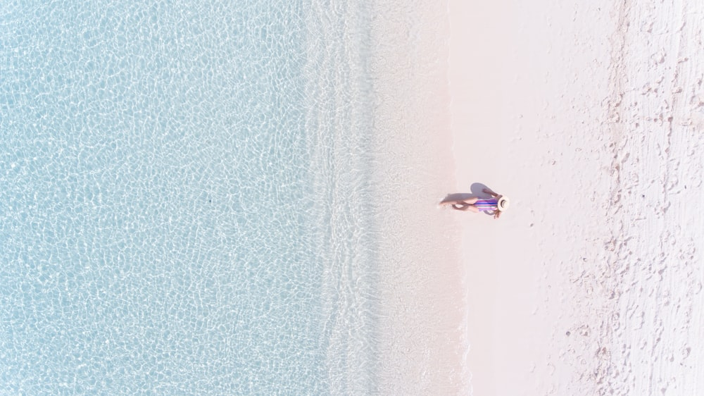 aerial view of person sitting on sand facing sea during daytime