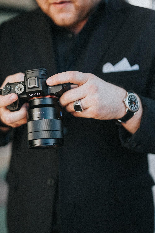 man holding black Sony DSLR camera