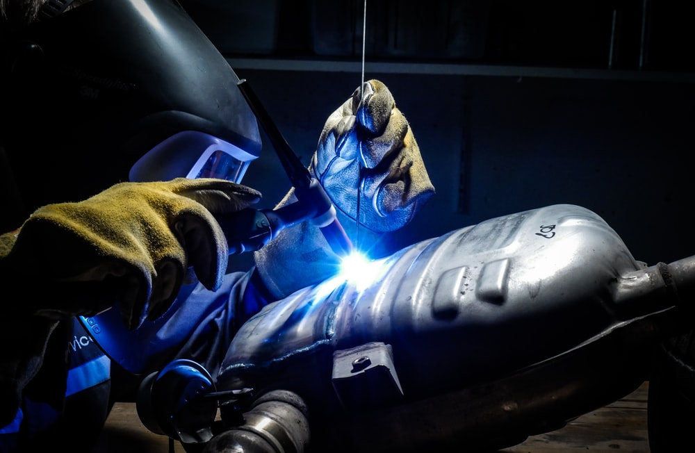 man wearing welding helmet welding on grey metal tank