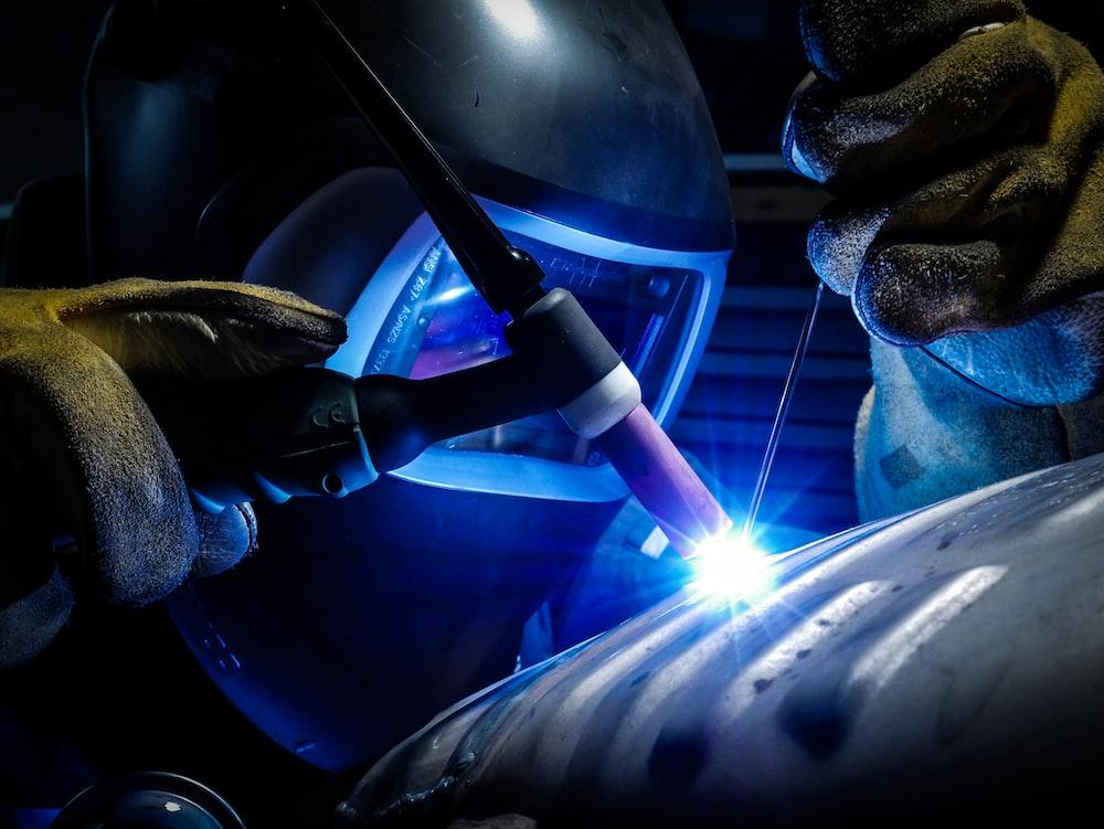 person welding gray metal equipment