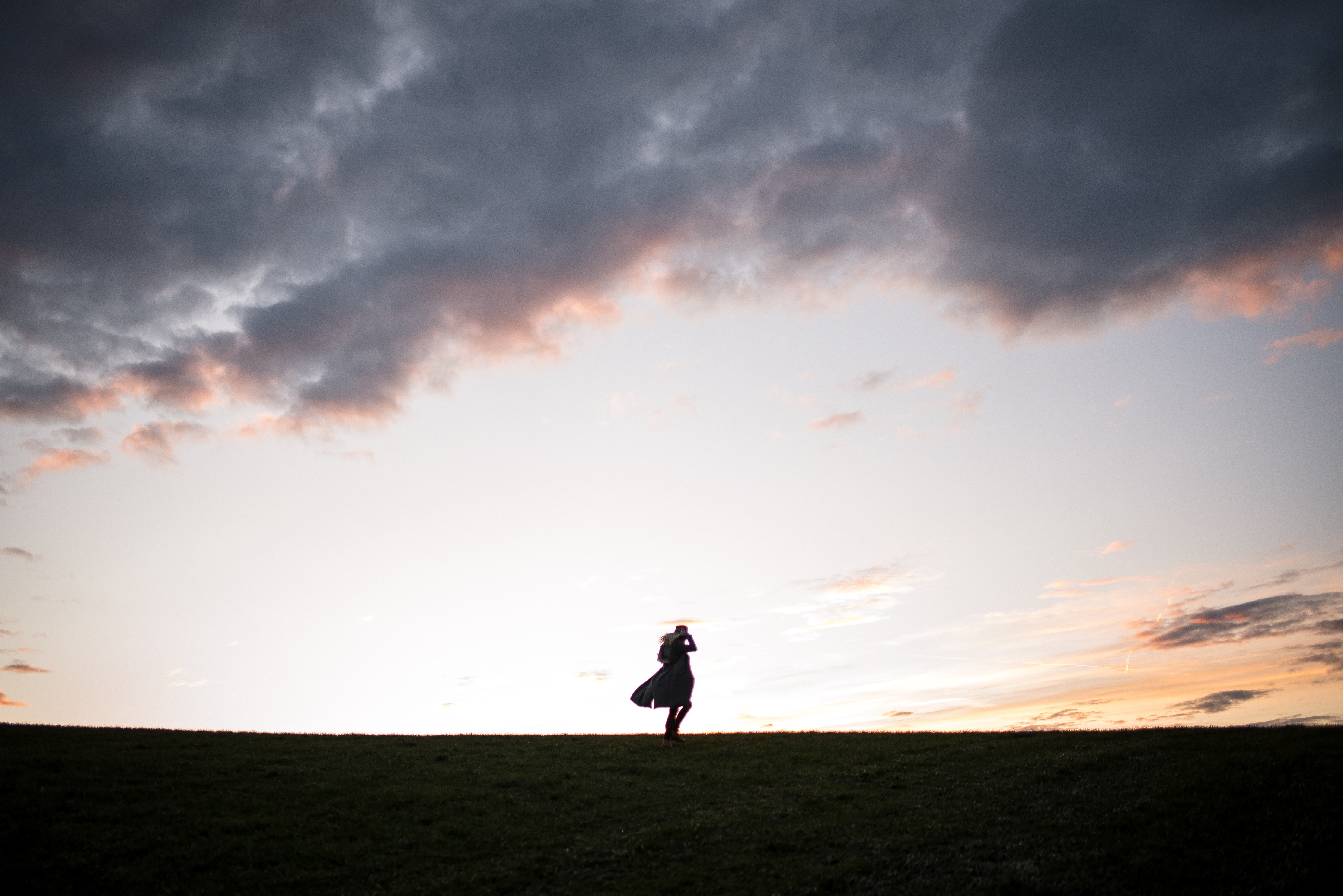 silhouette of man standing on ground under cloudy sky