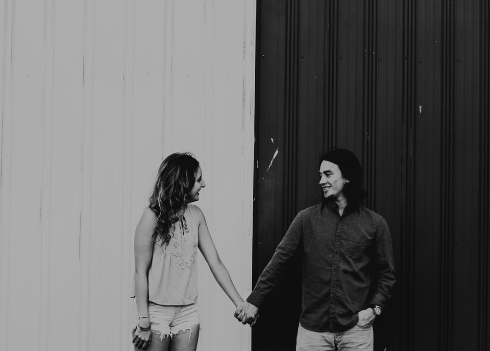 man and woman holding hands in grayscale photography