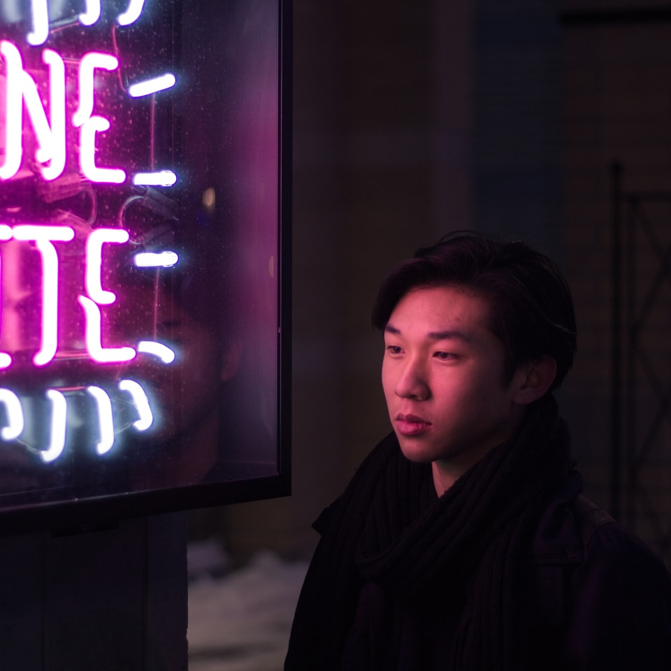 man standing beside pink and blue neon light signage