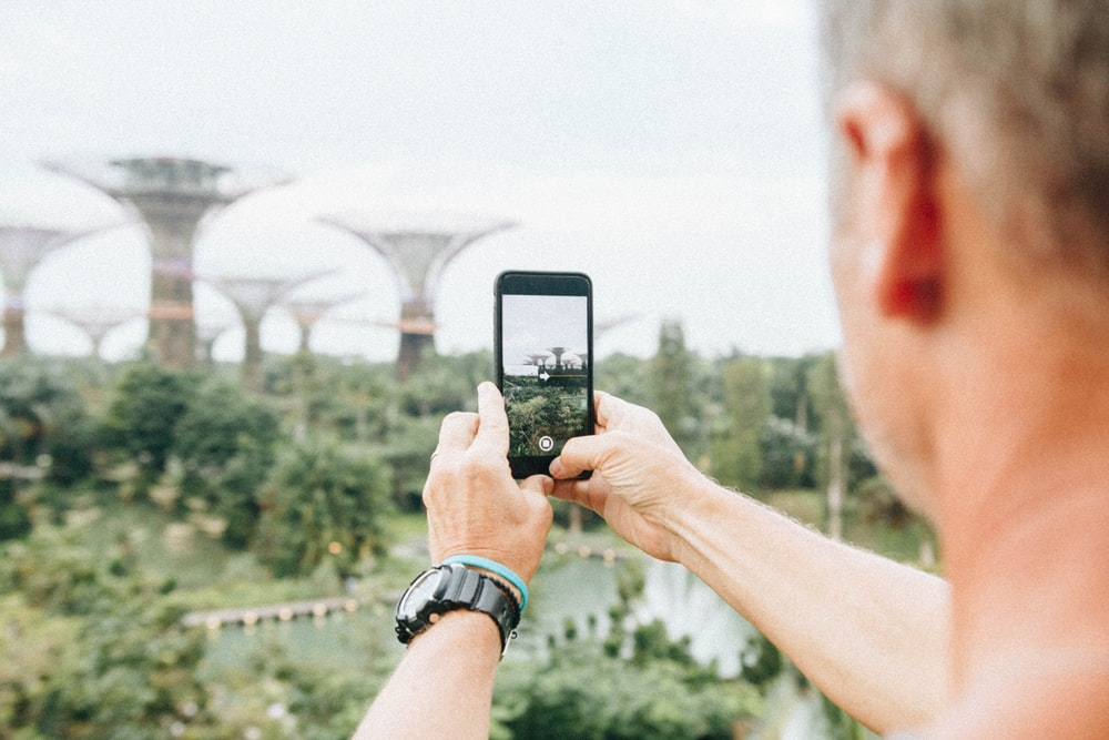 man taking picture using smartphone during daytime