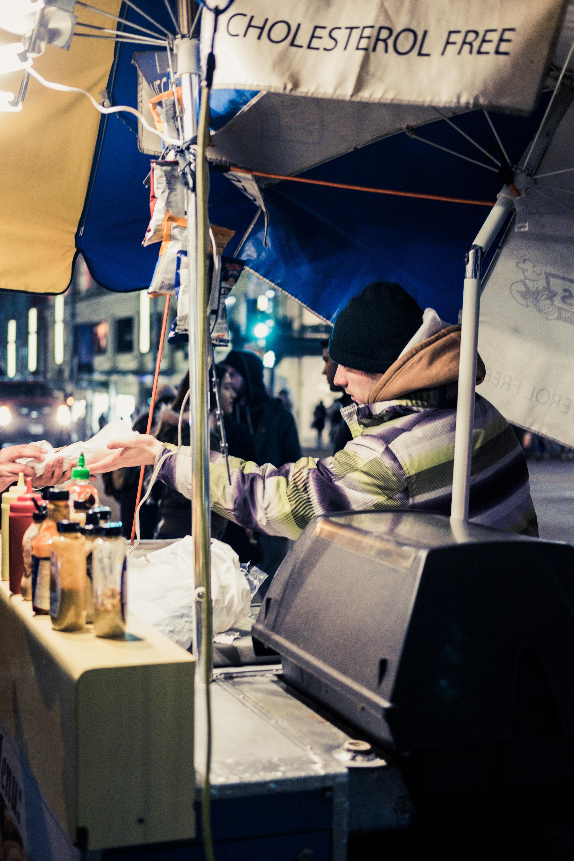 man under umbrella beside table