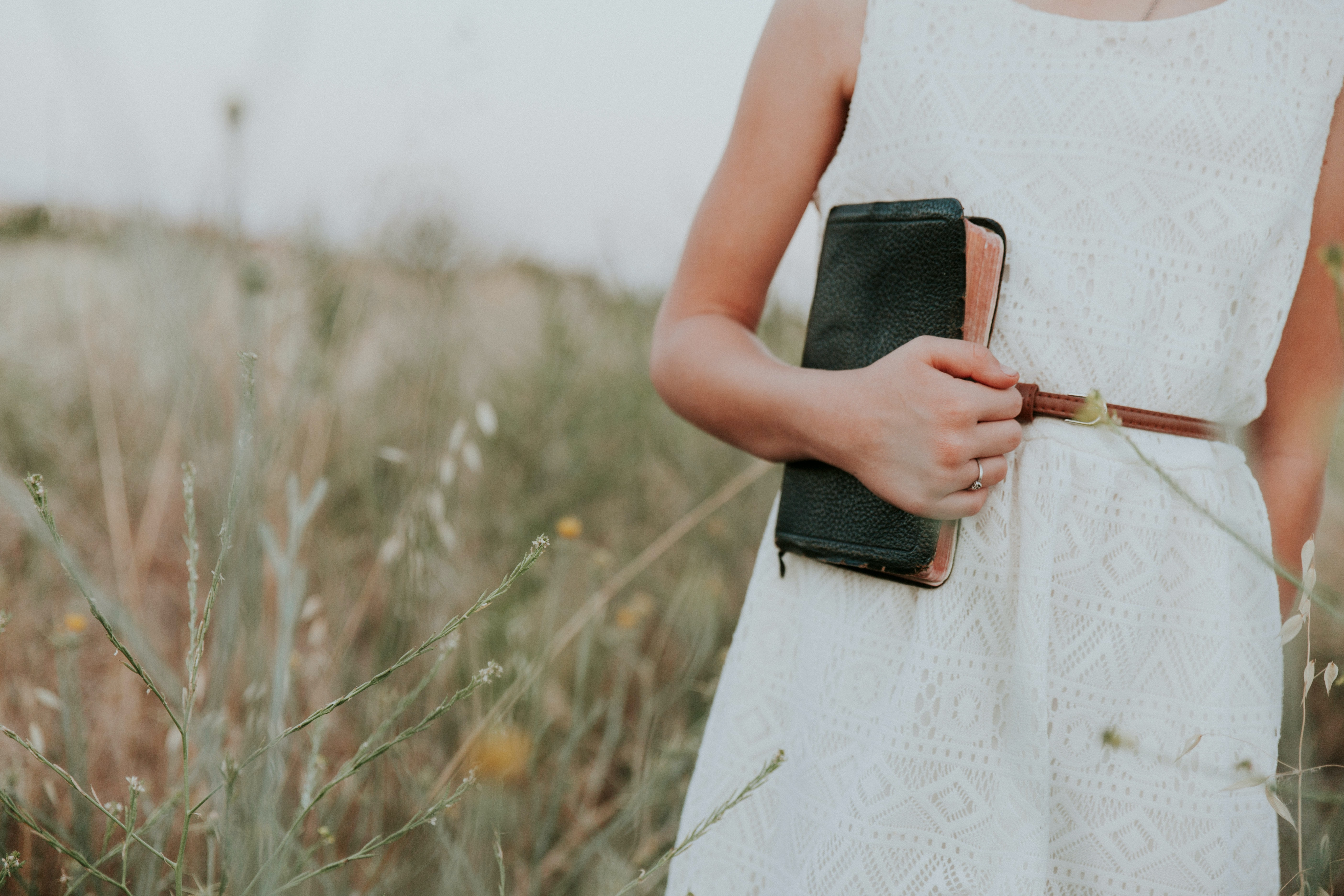 woman in white sleeveless dress holding book