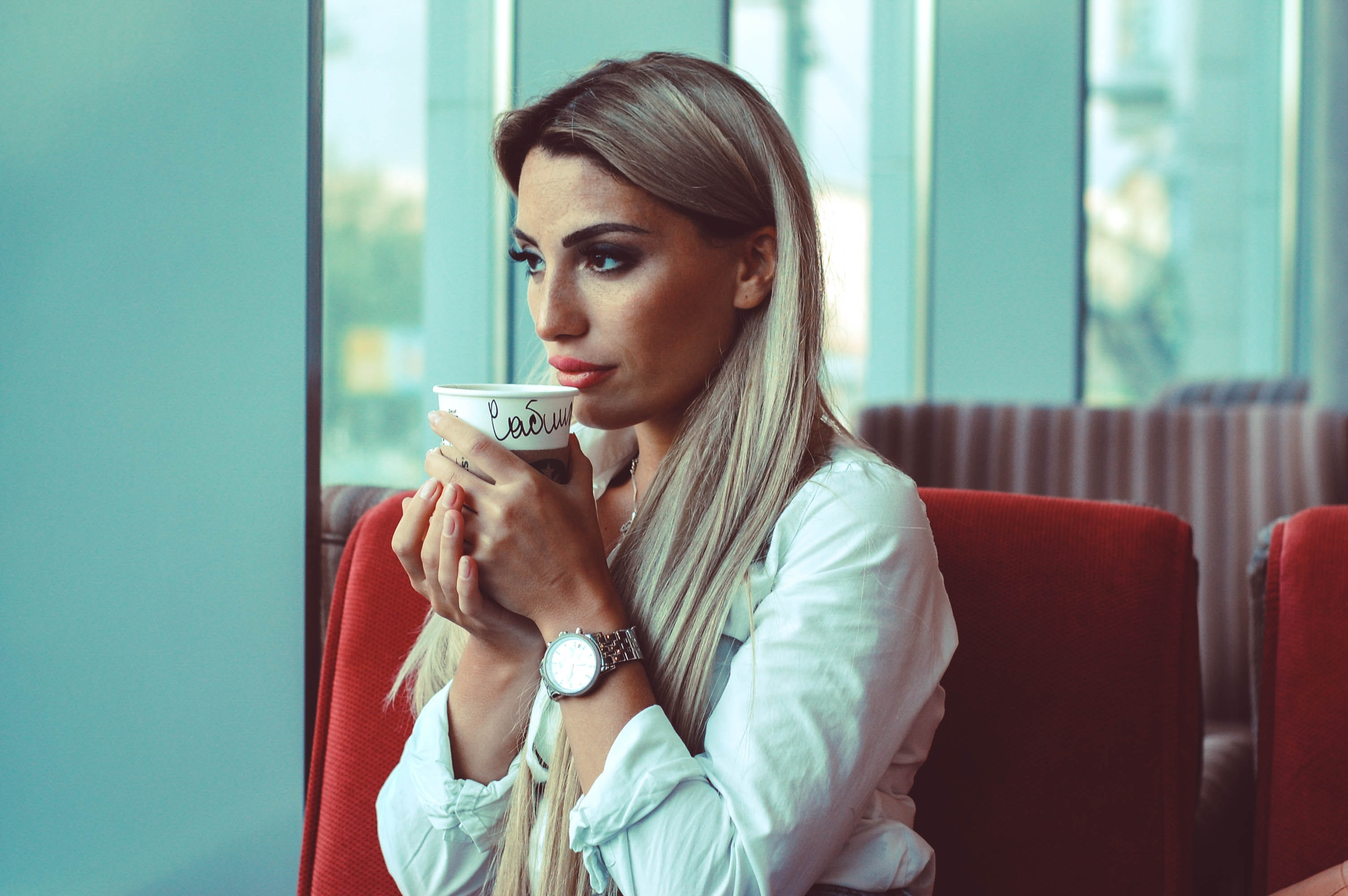 women sitting on chair holding cup of coffee