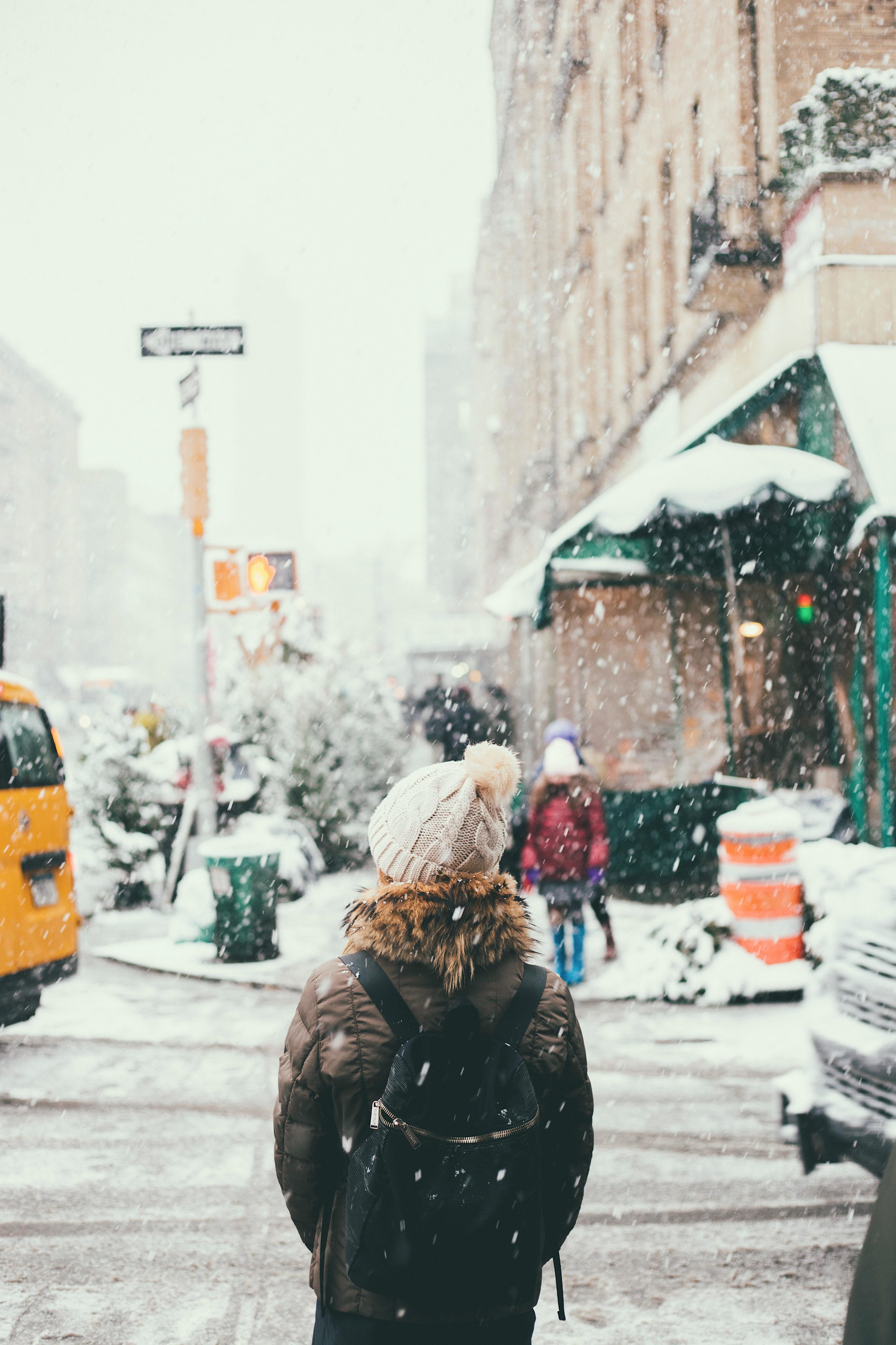 woman in brown jacket standing beside road
