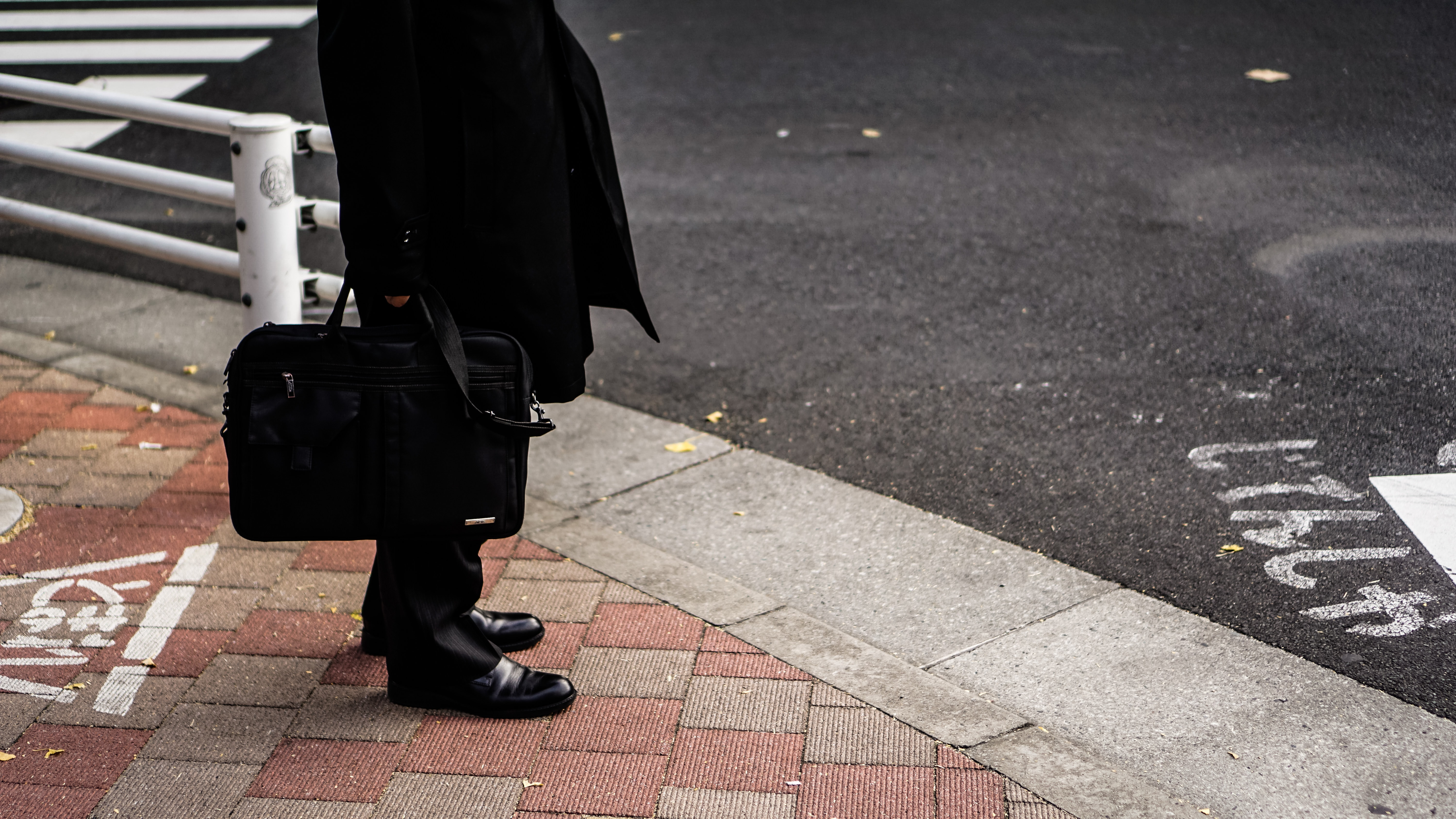 person in black dress shoes beside road