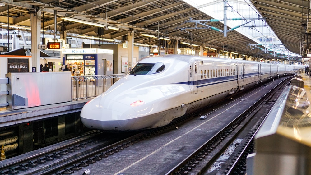 time lapse photography of white train shinkansen japan