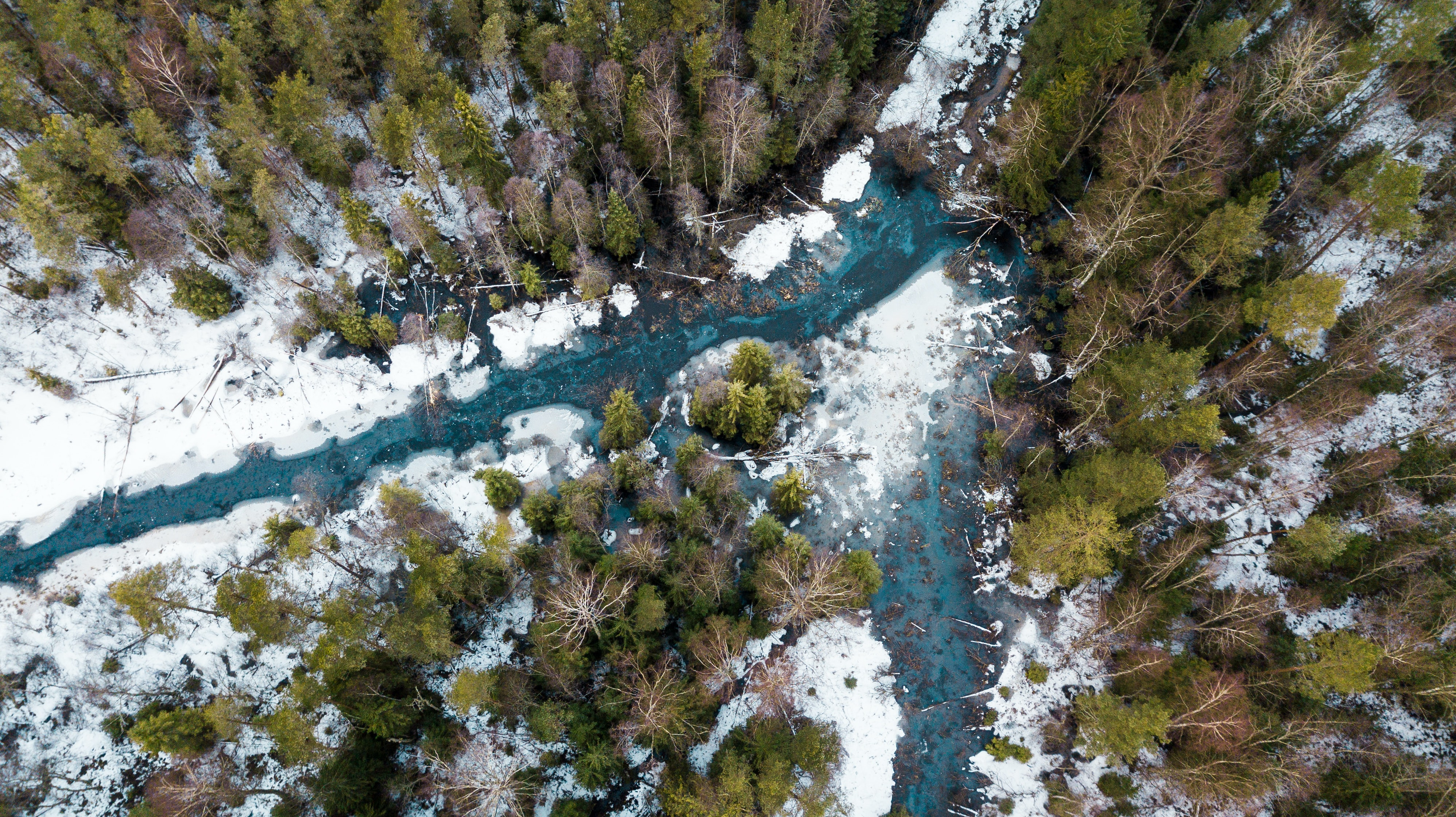 top view of frosted river surrounded with trees during daytime