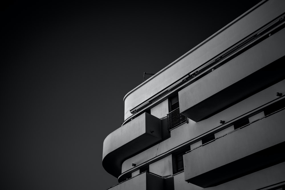low angle grayscale photo of concrete building